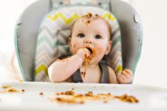Little baby eating her dinner and making a mess. A Little baby eating her dinner and making a mess stock photography