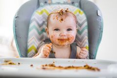 Little baby eating her dinner and making a mess Stock Photo