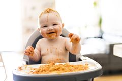 Little baby girl eating her spaghetti dinner and making a mess stock images