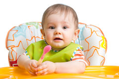 Little baby are eating. Kid boy sitting with spoon at table. Royalty Free Stock Photo