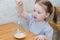Little baby eating oatmeal. Little child picks his spoon in his porridge royalty free stock photo