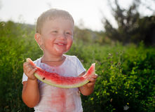 Little baby eating watermelon outdoors stock image