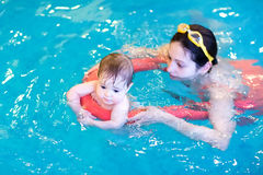 Little baby enjoying swimming pool with her mother. Adorable little baby enjoying swimming pool with her mother stock photography