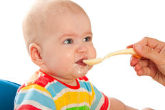 Little baby is feeding curds from spoon Royalty Free Stock Photos
