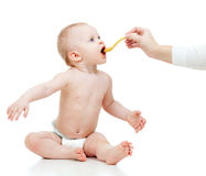 Little baby feeding with a spoon Royalty Free Stock Photos