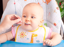 Little baby feeding with a spoon Royalty Free Stock Images