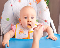 Little baby feeding with a spoon Royalty Free Stock Image