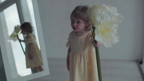 Little baby with flower in apartment. Happy girl stock video footage