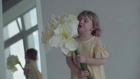 Little baby with flower in apartment. Happy girl stock footage