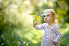 Little baby in a forest holding maples leaves Stock Photo