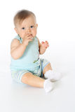 Little baby full-leight sitting and chewing nipple. Small kid wears blue T-shirt and striped pants full-leight sitting and chewing nipple white background Stock Photography