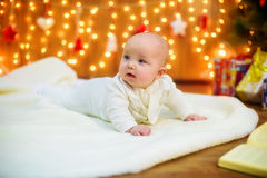 Little baby with gifts at Christmas tree Stock Image