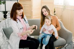 Little baby girl accepts to drink medicine syrup with spoon from family doctor at home. royalty free stock photo