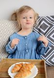 Little baby girl age of 1,11 years eating croissants Stock Photos