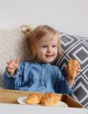 Little baby girl age of 1,11 years eating croissants Royalty Free Stock Image