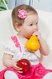 Little baby girl with apple and pear Stock Images