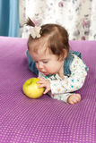Little baby girl with an apple smiling indoors Stock Photos