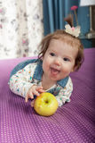 Little baby girl with an apple smiling Stock Photo