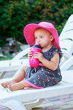 Little baby girl in autumn park drinks from pink plastic bottle.  Royalty Free Stock Image
