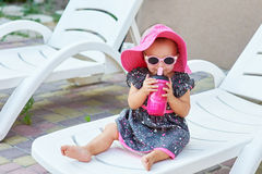 Little baby girl in autumn park drinks from pink plastic bottle.  Stock Images