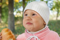Little baby girl in autumn park eats pie Stock Image