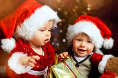 Santa babies with gift having fun Royalty Free Stock Photos