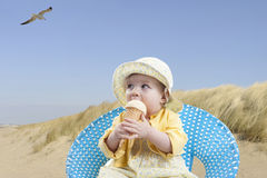 Little baby girl at the beach eating ice cream Royalty Free Stock Photography