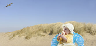 Little baby girl at the beach eating ice cream Stock Image