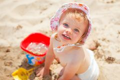 Baby girl beach. Little baby girl at the beach playing with sand toys royalty free stock photos