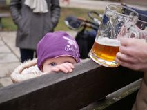 Little baby girl with a beer glass in the outdoor pub stock photo
