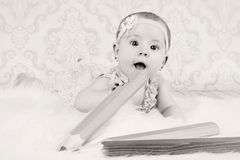 Little baby girl with big crayons Stock Photography