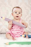 Little baby girl with big crayons Royalty Free Stock Photo