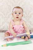 Little baby girl with big crayons Stock Image
