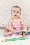 Little baby girl with big crayons Stock Image