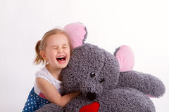 Little baby girl with big soft toy mouse with heart. Little girl with a huge soft mouse in an embrace, emotions, laughter Royalty Free Stock Photo
