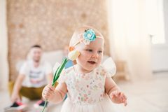 Little baby girl blonde with a bandage on her head holding a color tulbpin inside the house on the background of her parents. Dressed in a white fluffy dress Royalty Free Stock Images
