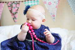 Little baby girl in blue dress with pink beads Royalty Free Stock Image