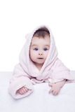 Little baby girl with blue eyes in pink bathrobe lying on her be Stock Photo