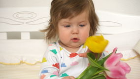 Little baby girl with bouquet of tulips stock video