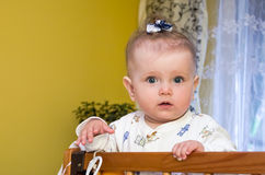 Little baby girl with bow on her head plays in the crib Stock Image
