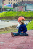 Little baby girl builder with the construction helmet and poster Stock Image