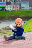 Little baby girl builder with the construction helmet and poster Royalty Free Stock Images