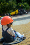 Little baby girl builder with the construction helmet and poster Stock Images