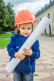 Little baby girl builder with the construction helmet and poster Stock Photography