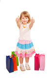 Little girl buyer with shopping bags showing a thumbs up or OK s Royalty Free Stock Image
