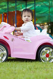 A little baby girl in Car Toy pink color Royalty Free Stock Images