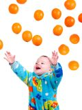 Little baby girl caughts flying oranges Stock Photos