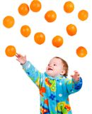 Little baby girl caughts orange Stock Image