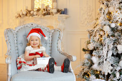 Little Baby Girl Charming Blonde In A Red Santa Hat, Smiling And Royalty Free Stock Images