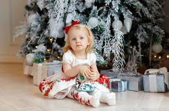 Little baby girl charming blonde in a red dress sitting beside a Stock Photography